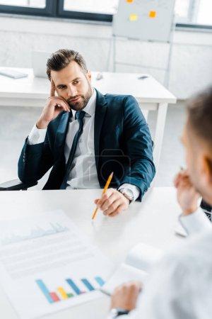 Photo pour Homme d'affaires barbu tenant crayon et regardant collègue assis au bureau - image libre de droit