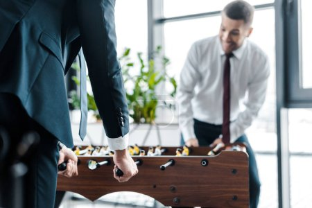 selective focus of businessmen playing table football in modern office