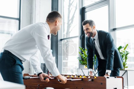 cheerful businessmen playing table football in modern office