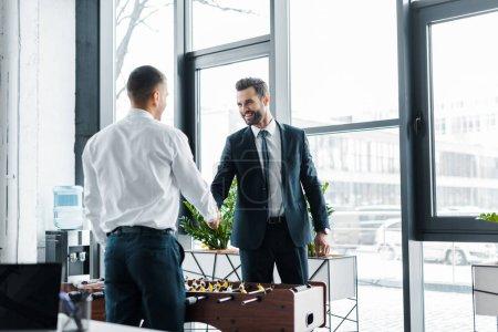Photo pour Hommes d'affaires heureux se serrant la main près de baby foot dans le bureau moderne - image libre de droit
