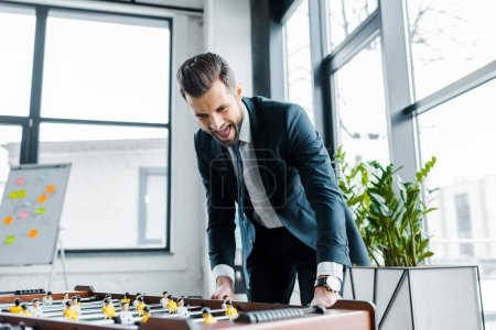 Photo for Excited bearded businessman in formal wear playing table football - Royalty Free Image