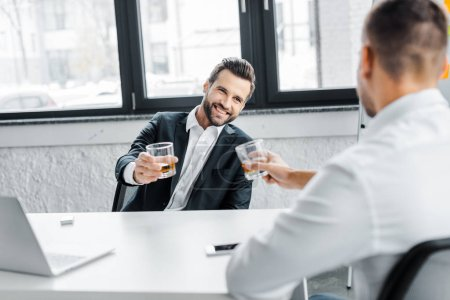 Photo for Cheerful businessman holding glass of whiskey while looking at coworker - Royalty Free Image