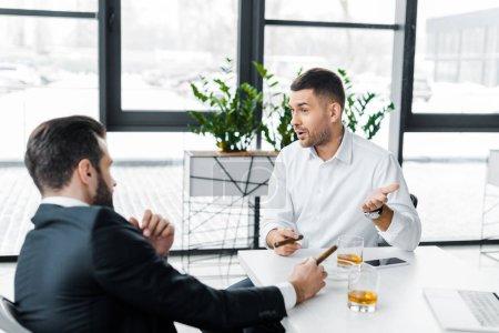 Photo pour Hommes d'affaires formelle portent fumer des cigares cubains dans le bureau moderne - image libre de droit