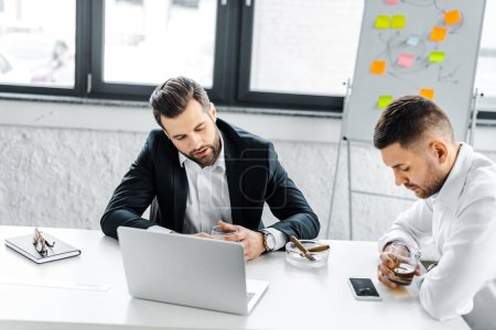Photo pour Fatigué des hommes d'affaires ayant la discussion dans le bureau moderne - image libre de droit