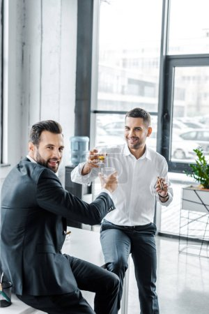 Photo for Smiling businessmen toasting with glasses of whiskey - Royalty Free Image