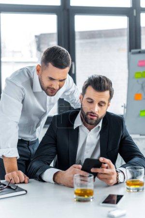 Photo pour Hommes d'affaires beau regarder smartphone dans le bureau moderne - image libre de droit