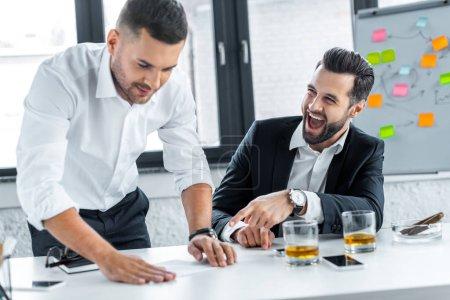 Photo pour Homme d'affaires barbu riant près de collègue dans le bureau moderne - image libre de droit