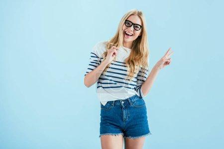 Studio shot of joyful girl holding toy glasses and showing peace sign on blue background