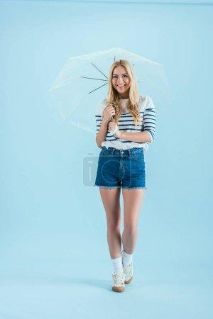 Photo for Joyful blonde girl holding umbrella on blue background - Royalty Free Image