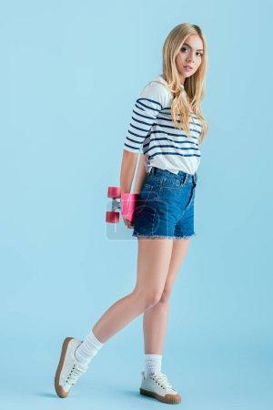 Photo for Slim blonde girl holding longboard on blue background - Royalty Free Image