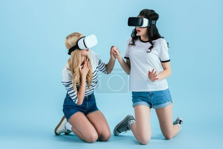 Photo for Scared girls in VR headset standing on knees and holding hands on blue background - Royalty Free Image