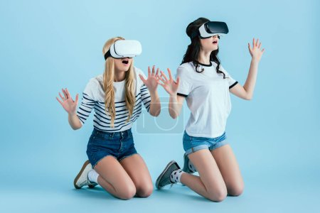 Photo for Studio shot of amazed girl in VR headset standing on knees on blue background - Royalty Free Image