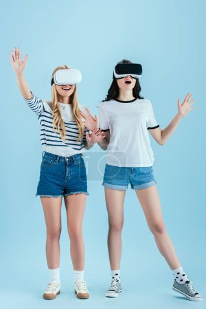 Photo for Excited girls posing in VR headset isolated on blue background - Royalty Free Image