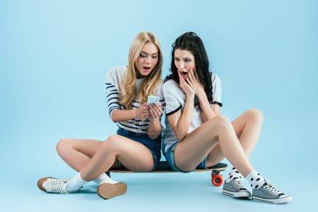 Photo pour Filles surprises regardant l'écran du smartphone assis sur longboard sur fond bleu - image libre de droit
