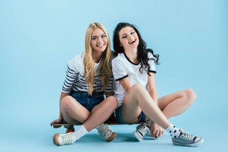 Photo pour Belles jeunes femmes assises sur longboard sur fond bleu - image libre de droit