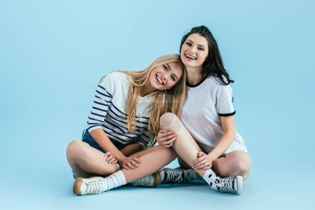 Photo for Laughing girls sitting on floor with legs folded on blue background - Royalty Free Image