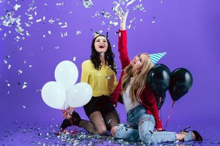 Foto de Chicas riendo en sombreros del partido sosteniendo globos y tirar confeti sobre fondo púrpura - Imagen libre de derechos