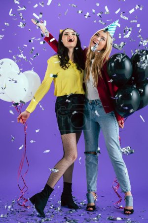 Attractive girls with balloons laughing under confetti on purple background