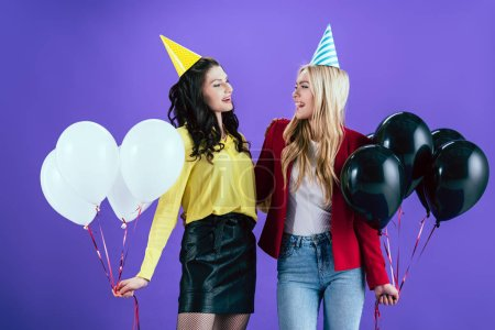 Cheerful girls in party hats holding balloons and looking at each other on purple background