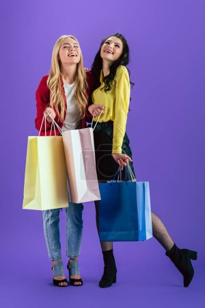 Photo for Cheerful girls posing with colorful shopping bags on purple background - Royalty Free Image