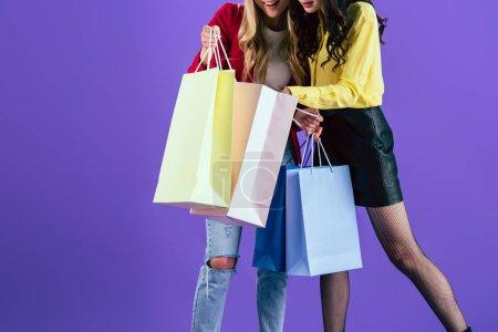 Photo pour Vue recadrée des filles qui regardent dans des sacs à provisions sur fond violet - image libre de droit