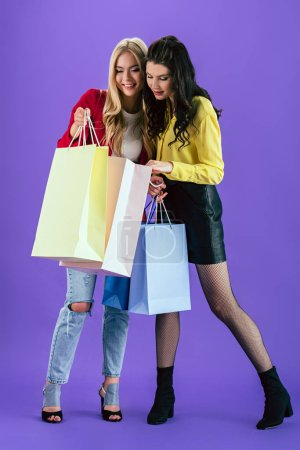 Photo for Curious girls looking in shopping bags on purple background - Royalty Free Image