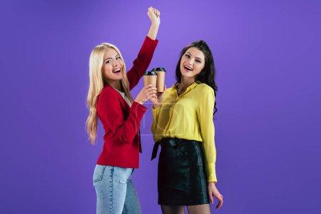 Photo pour Rire des filles tinter les tasses de café sur fond violet - image libre de droit