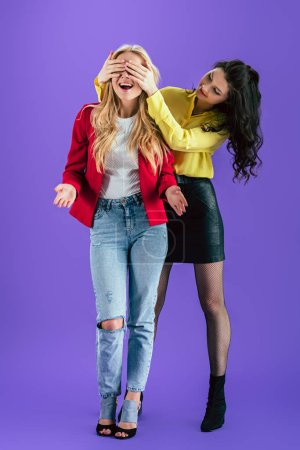 Foto de Dos chicas con estilo bromeando sobre fondo púrpura - Imagen libre de derechos