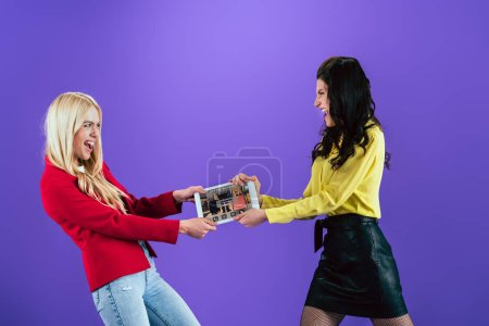Photo for Angry girls fighting for digital tablet with online booking app on screen on purple background - Royalty Free Image
