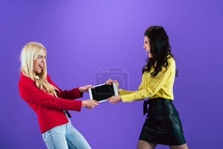 Photo for Girls screaming and fighting for digital tablet with blank screen on purple background - Royalty Free Image