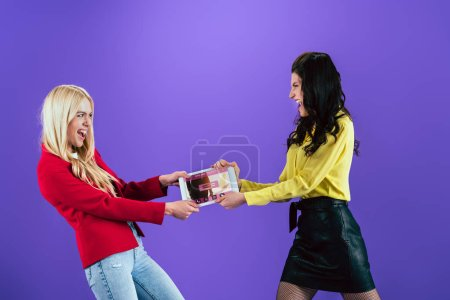 Photo pour Cris de jeunes femmes tenant une tablette numérique avec des billets en ligne app à l'écran sur fond violet - image libre de droit