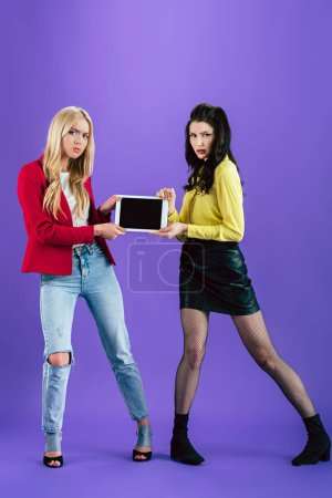 Photo for Full length view of irritated girls holding digital tablet with blank screen on purple background - Royalty Free Image