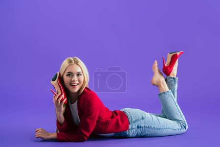 Photo for Gorgeous smiling girl in red high-heeled shoes lying on floor and looking at camera on purple background - Royalty Free Image