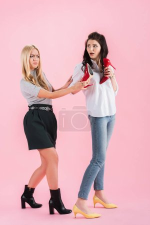 Photo for Unhappy women posing with red shoes on pink background - Royalty Free Image