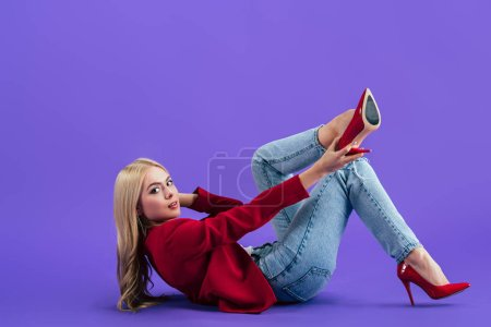 Photo for Stylish woman lying on floor and putting on high-heeled shoes on purple background - Royalty Free Image
