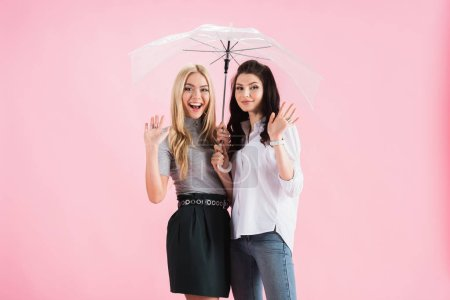 Happy girls holding umbrella and waving hands on pink background