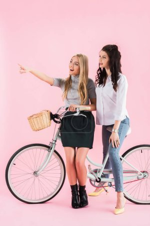 Photo for Laughing blonde girl pointing with finger while sitting on bicycle with friend on pink background - Royalty Free Image