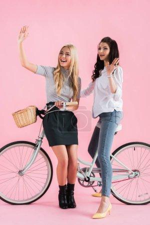 Photo pour Filles heureuses agitant les mains tout en étant assis sur le vélo sur fond rose - image libre de droit