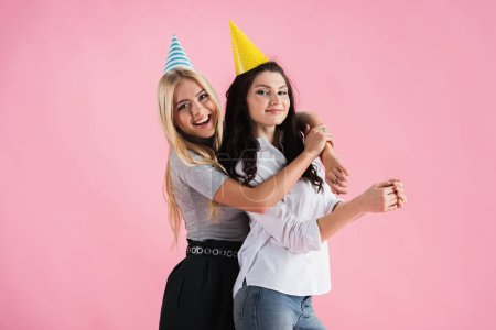 Photo for Joyful girls in party hats embracing with smile isolated on pink - Royalty Free Image
