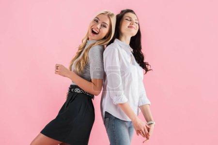 Photo pour Filles étonnantes souriant et posant dos à dos isolé sur rose - image libre de droit