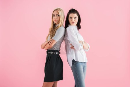 Photo for Upset young women posing with crossed arms isolated on pink - Royalty Free Image
