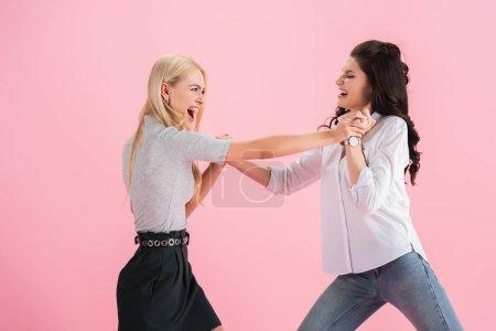 Photo pour Filles agressives hurlant et se battant isolé sur rose - image libre de droit