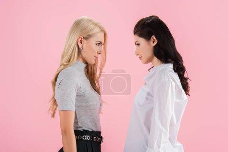 Photo pour Malheureuses jeunes femmes regardant l'autre isolé sur Rose - image libre de droit