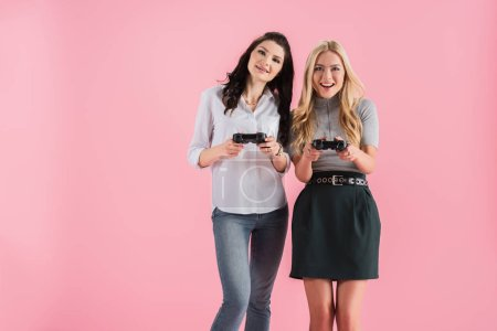 Photo for Excited girls with joysticks playing video game isolated on pink - Royalty Free Image