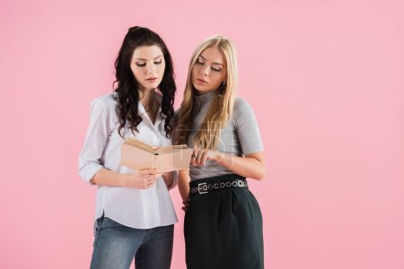 Studio shot of interested girls reading book isolated on pink