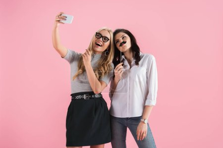 Photo for Girls with fake mustache and glasses taking selfie isolated on pink - Royalty Free Image