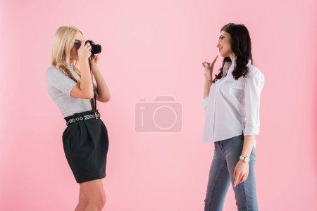 Photo pour Jeune fille blonde prise de photos tout en jeune fille brune, montrant le signe de la paix, isolé sur Rose - image libre de droit