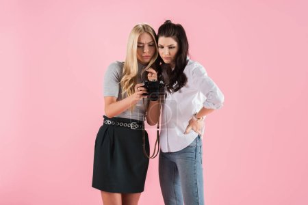Photo pour Concentré des filles regarder des photos sur l'appareil photo numérique isolé sur Rose - image libre de droit