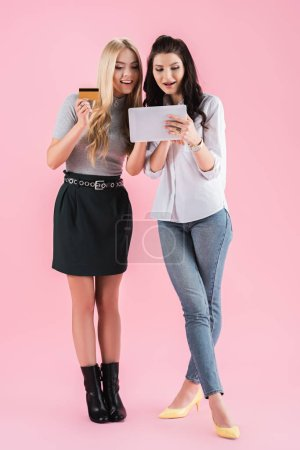 Photo for Interested girls with credit card looking at digital tablet screen on pink background - Royalty Free Image