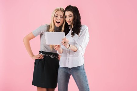 Photo for Amazed cheerful girls using digital tablet isolated on pink - Royalty Free Image
